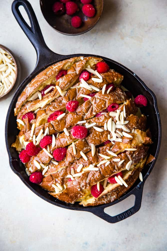 cast iron pan with unbaked raspberry almond french toast