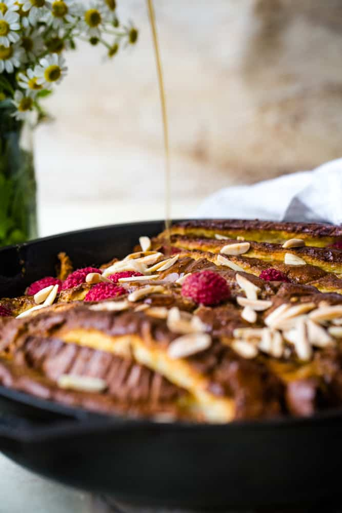 pouring syrup onto raspberry almond baked french toast