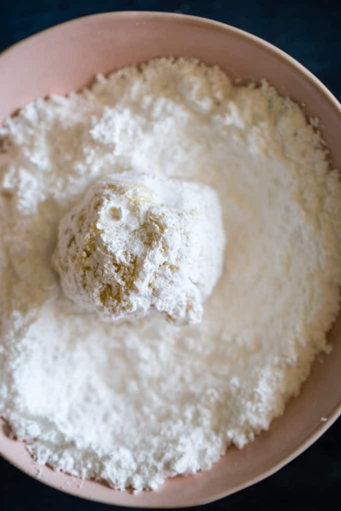 rolling the dough ball in a bowl of powdered sugar