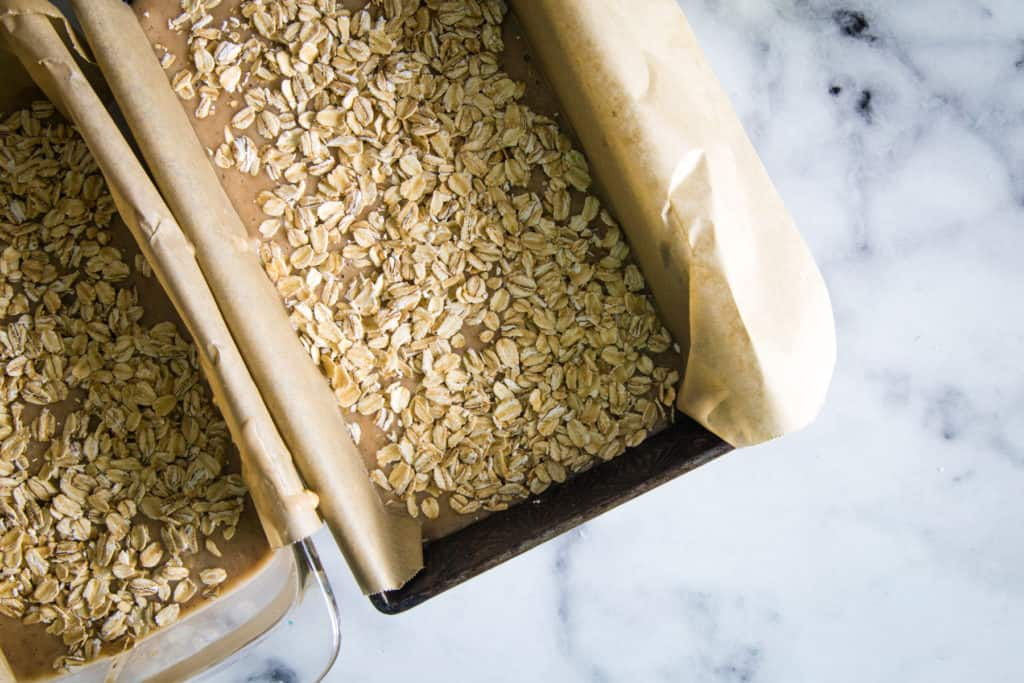two pans of applesauce oatmeal bread batter on marble background
