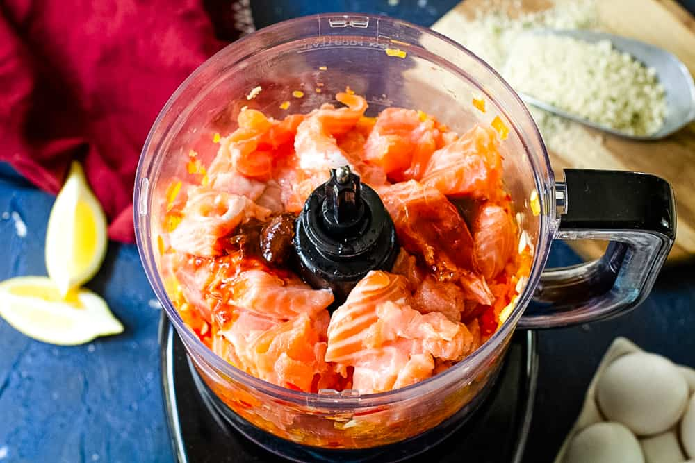 food processor with raw salmon and peppers inside