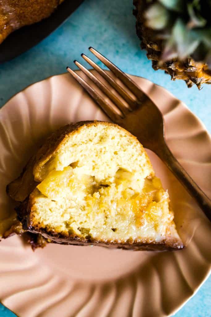 slice of upside down pineapple bundt cake on pink plate