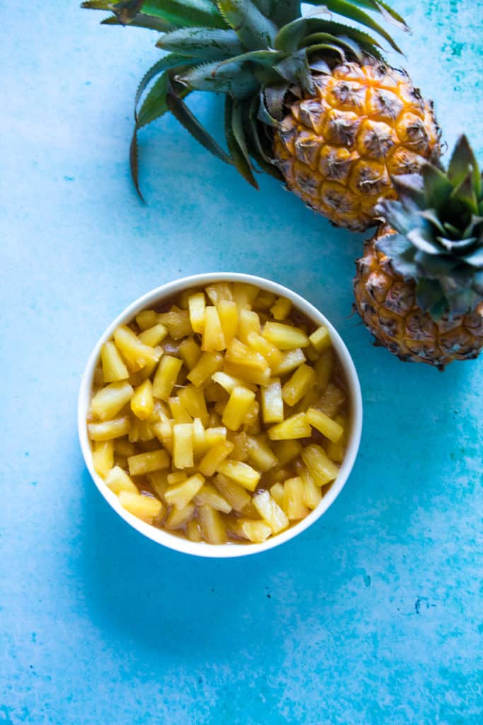 caramelized pineapple in white bowl on blue background