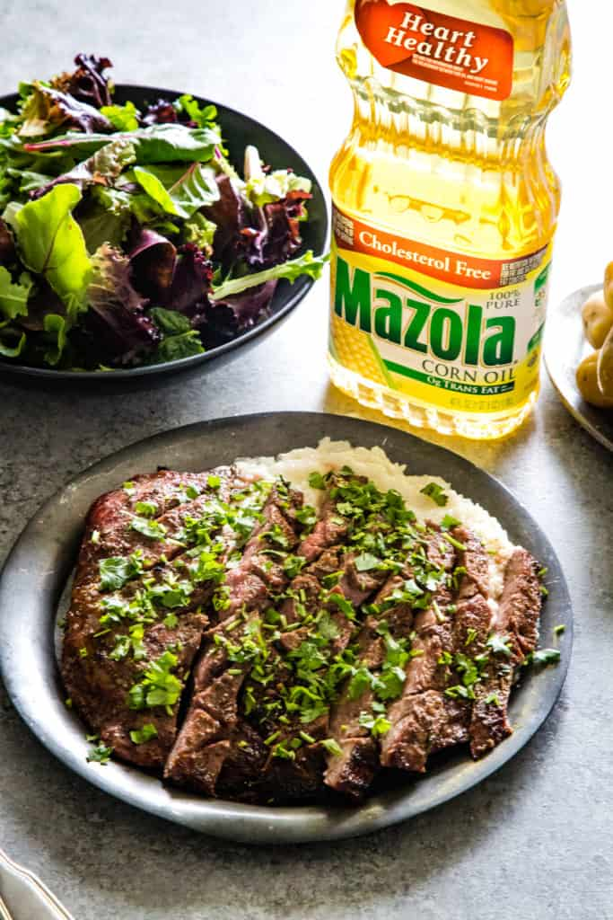 plate with grilled flank steak slices and bottle of oil in background