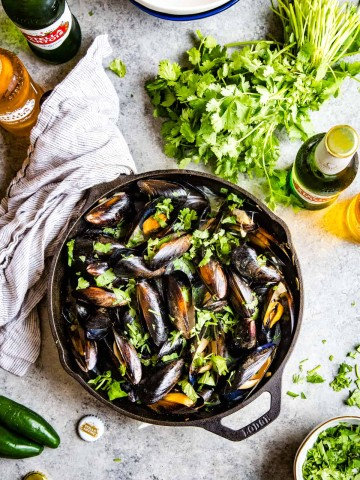 top down shot of cilantro beer broth mussels in cast iron skillet