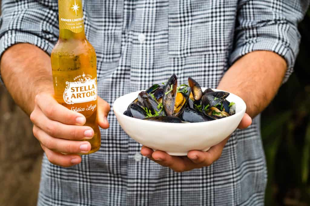 hands holding a bottle of stella artois and a white bowl of mussels