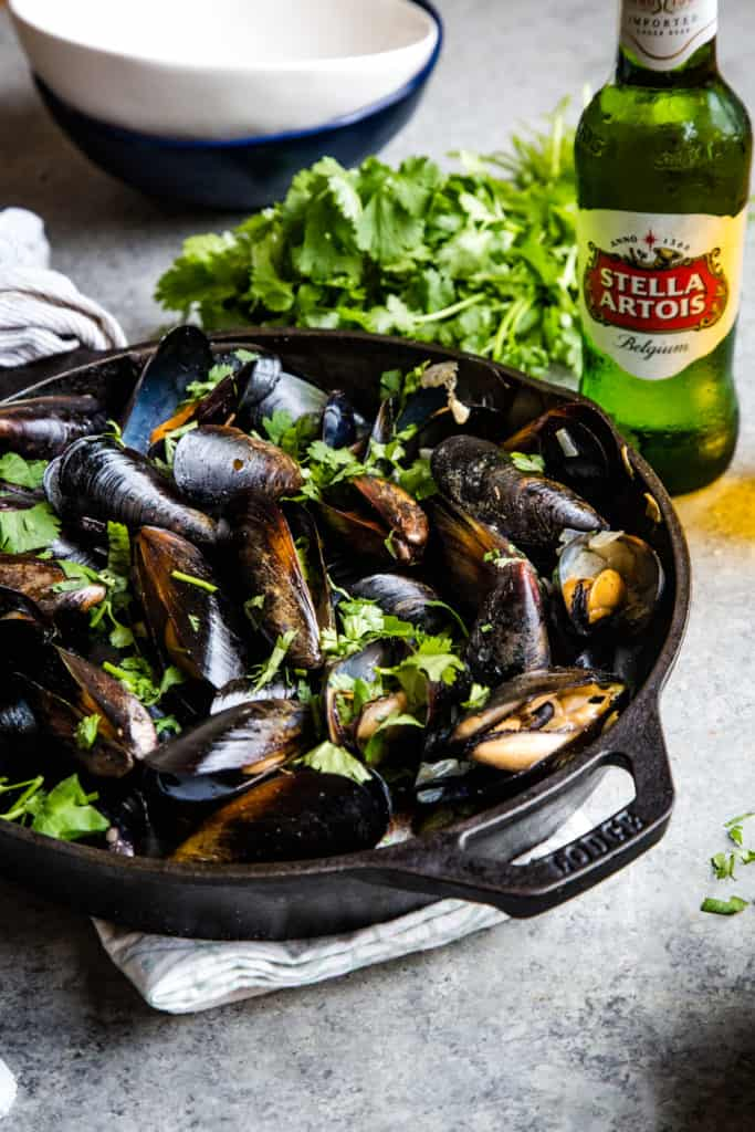 skillet with steamed cilantro beer broth mussels