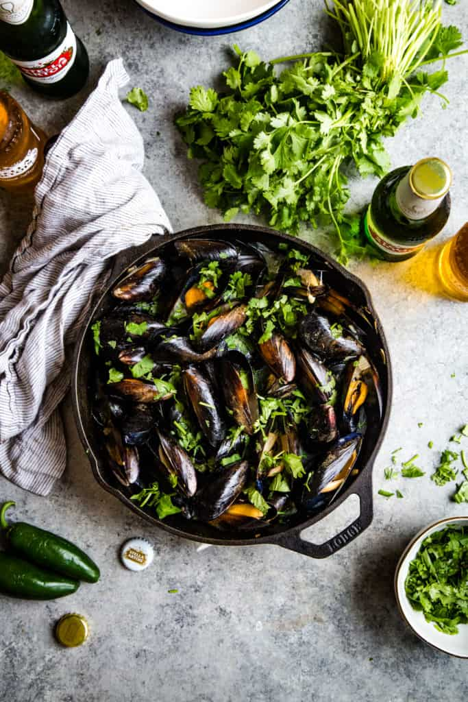 skillet with cooked mussels on metal background