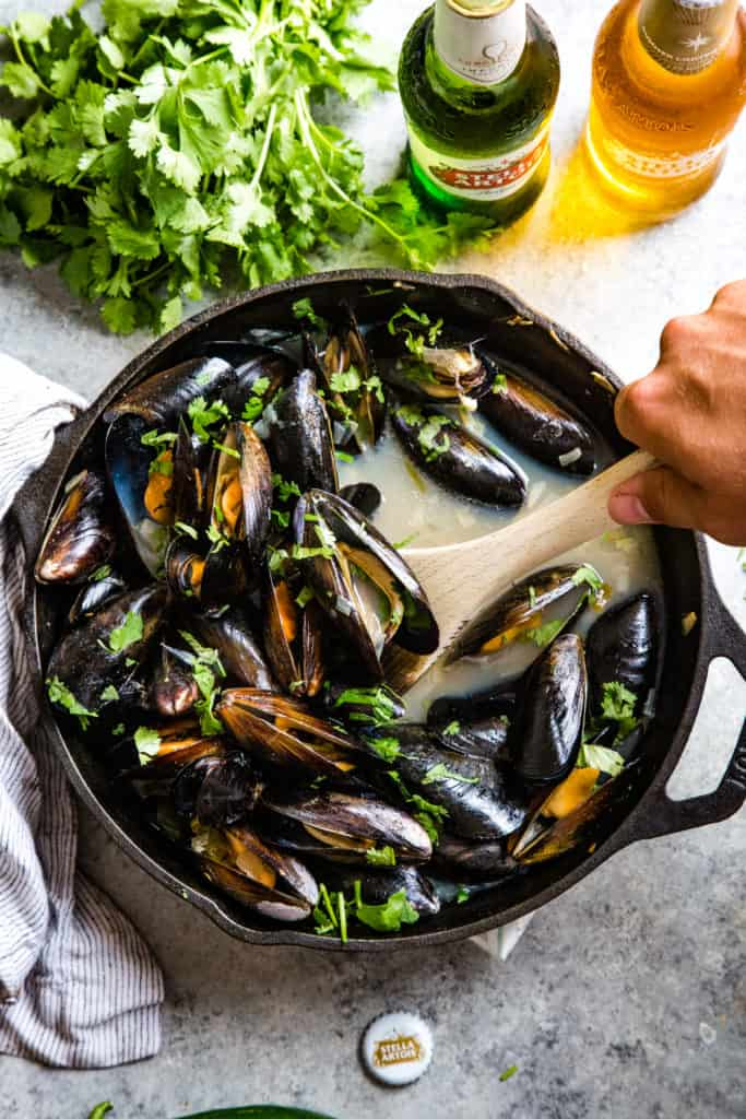 hand scooping out cooked mussels in cast iron skillet