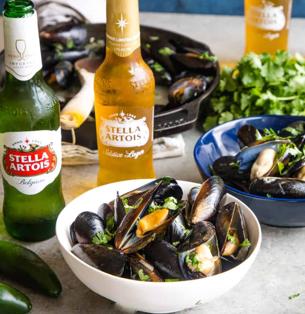 bowls of cooked mussels with bottles of stella artois beer in background