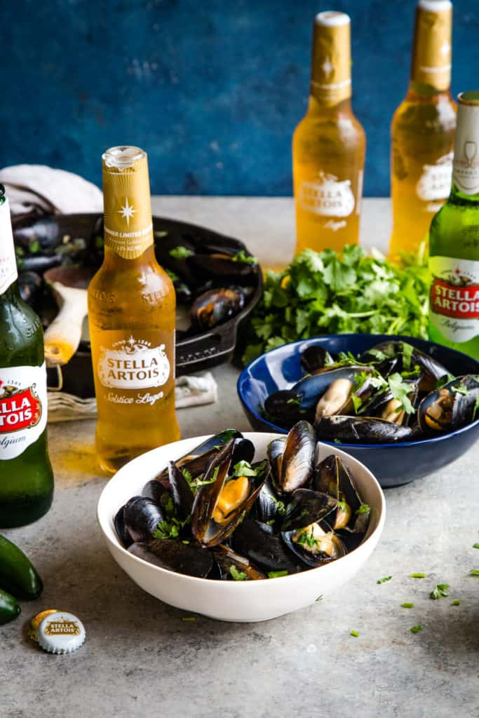 white bowl of cooked mussels with bottles of stella artois in background