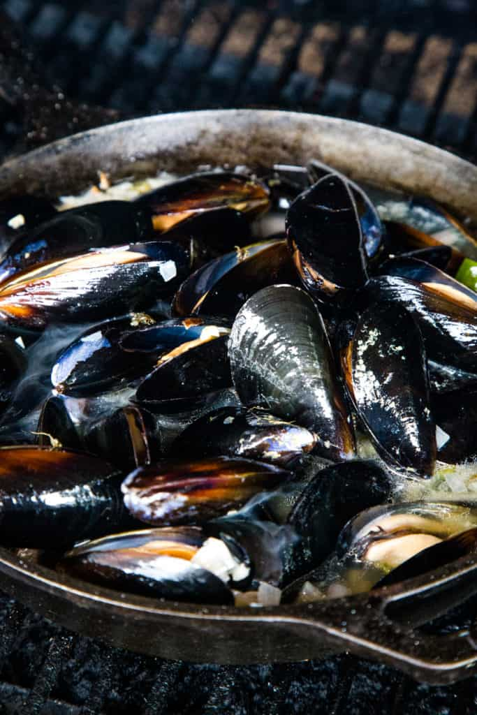 raw mussels cooking in skillet over grill