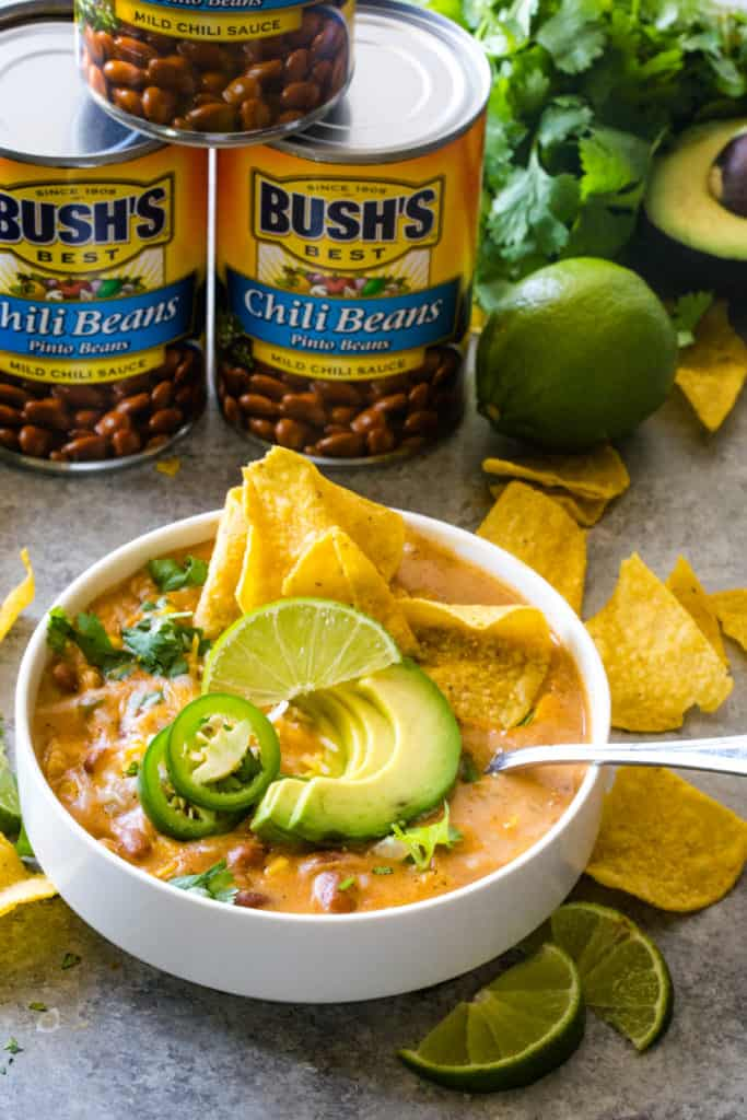white bowl of chicken jalapeno chili with 3 cans of bush's beans in background