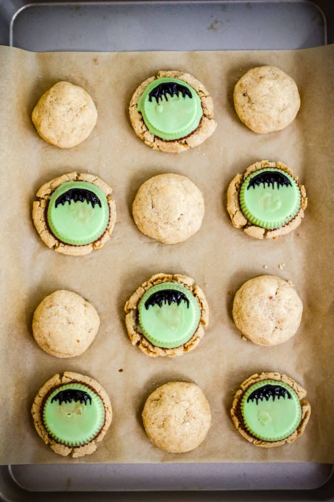 decorating the frankenstein cookies on a baking tray with black food gel