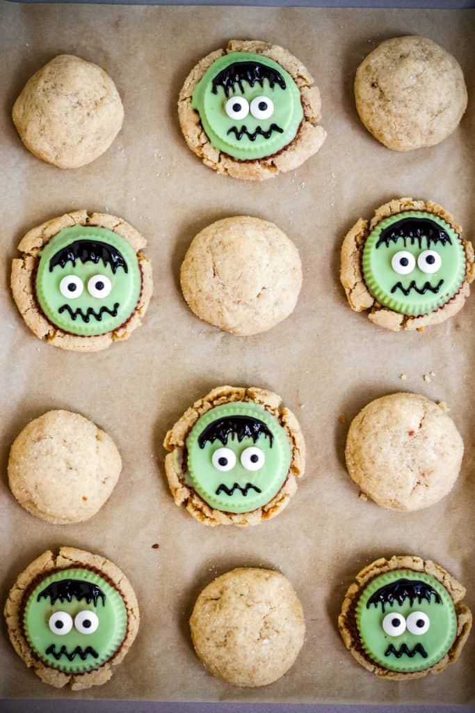 frankenstein peanut butter cookies on a parchment lined baking sheet