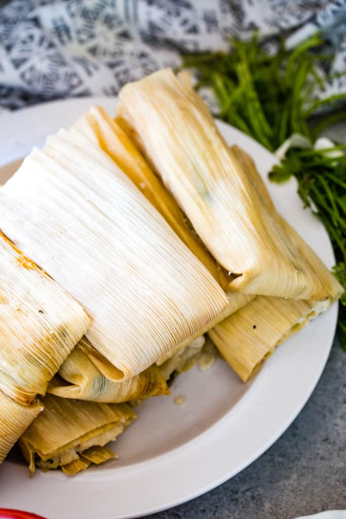 plate of cooked tamales in corn husks