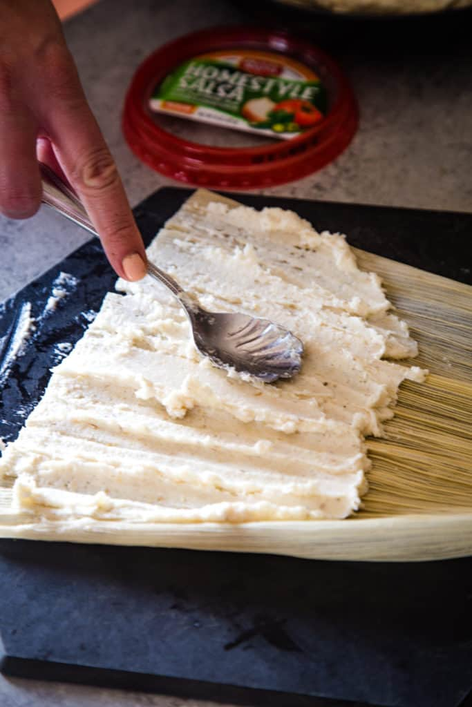 spreading the masa on the corn husk