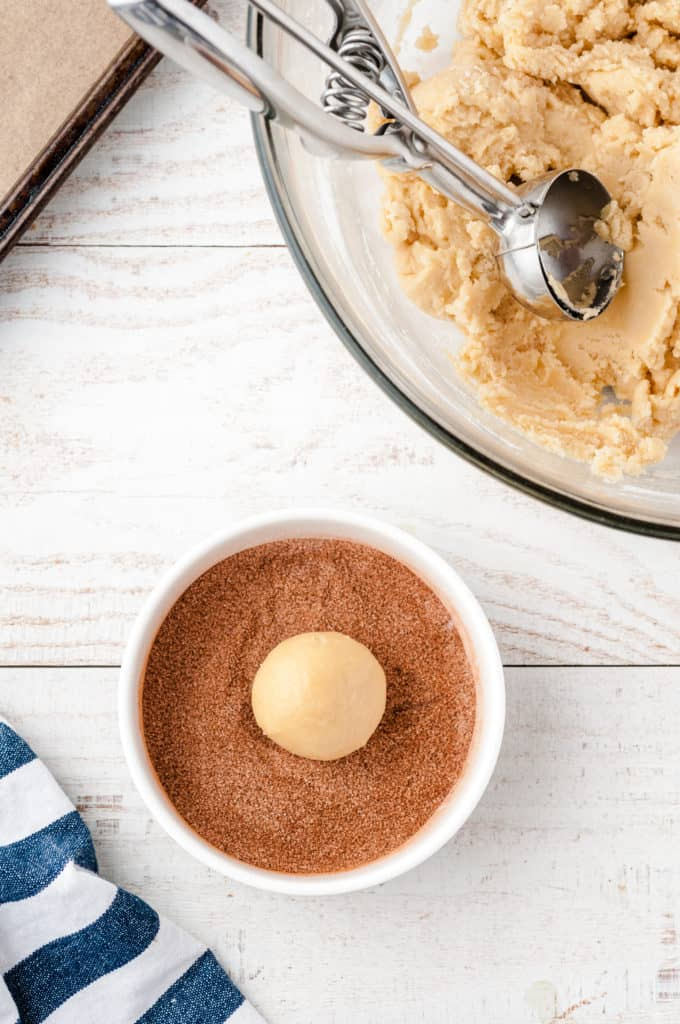 bowl of cinnamon and sugar with cookie dough ball in center