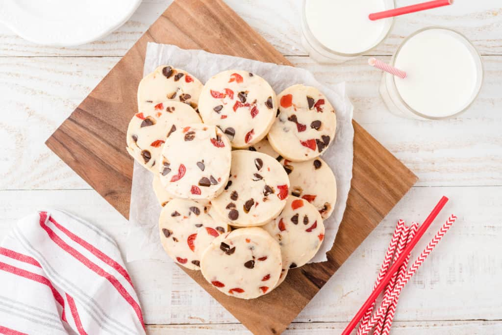 plate of chocolate cherry shortbread cookies on wood cutting board