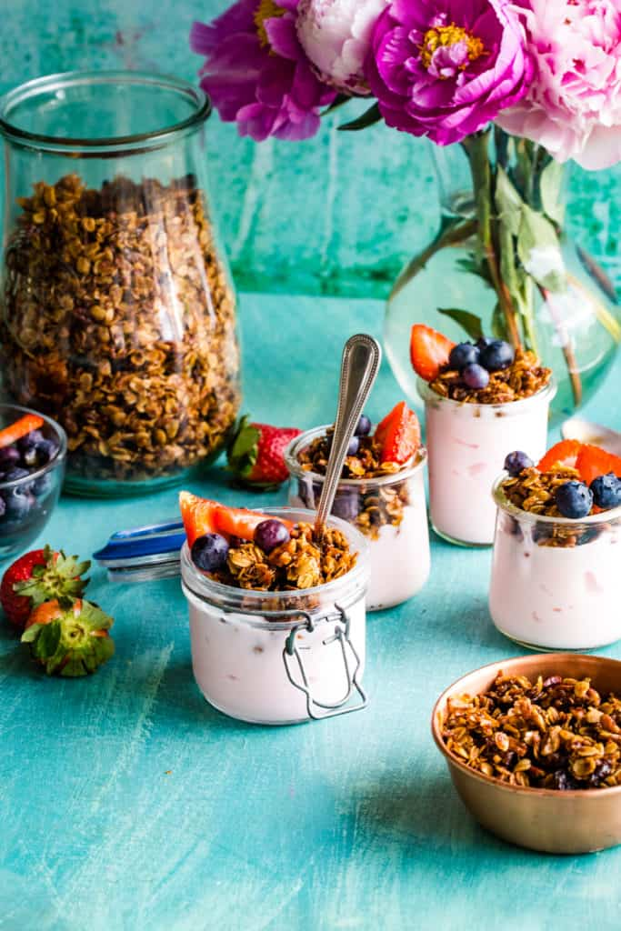 small jars of yogurt parfaits with large jar of granola in background