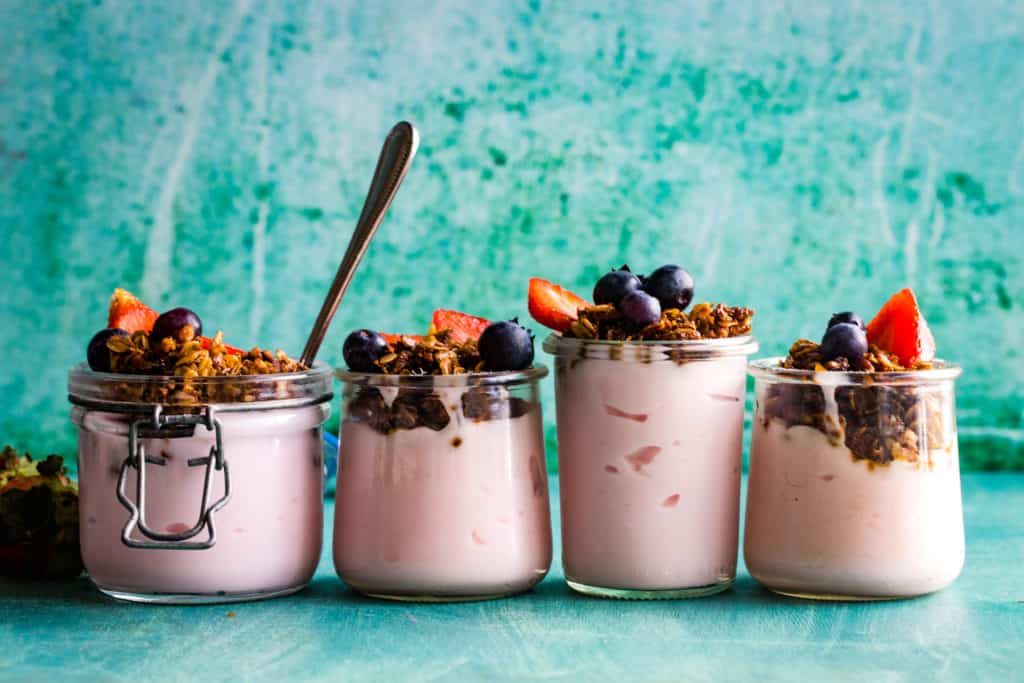 four jars of yogurt parfait with granola and berries lined up
