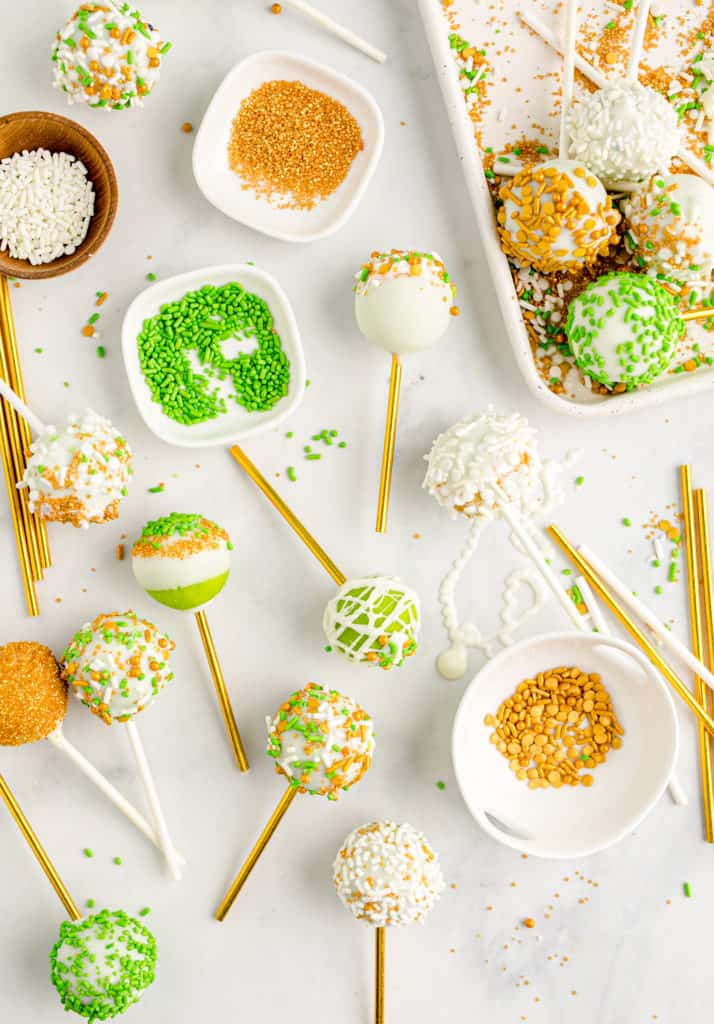 green cake pops and little bowls of sprinkles on white background
