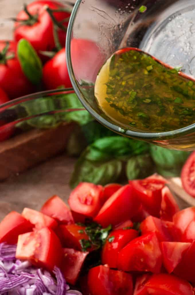 pouring dressing over tomato and onion salad