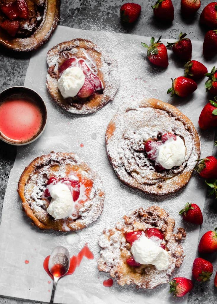 overhead shot of funnel cakes with strawberries and whipped cream