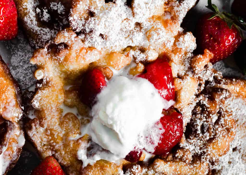 up close shot of funnel cake with strawberries and whipped cream