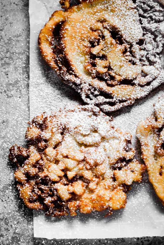 funnel cakes with powdered sugar on metal background