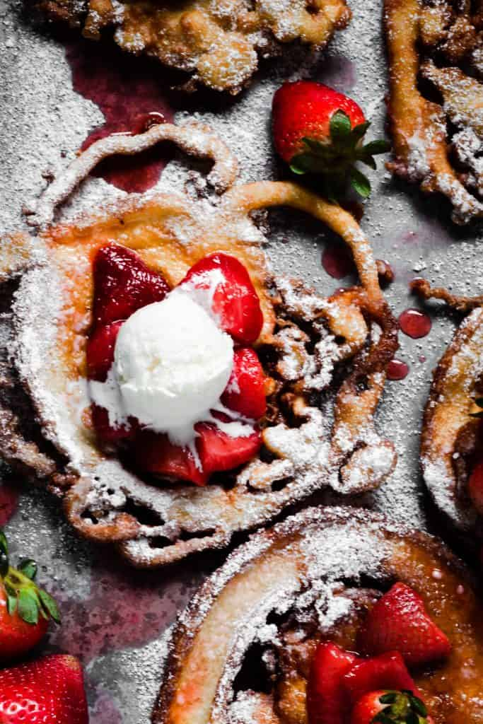 overhead shot of strawberry funnel cake with dollop of whipped cream