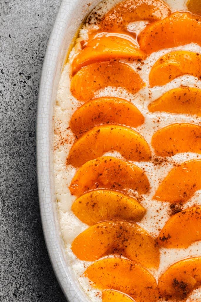 peaches on peach cobbler in white pan unbaked