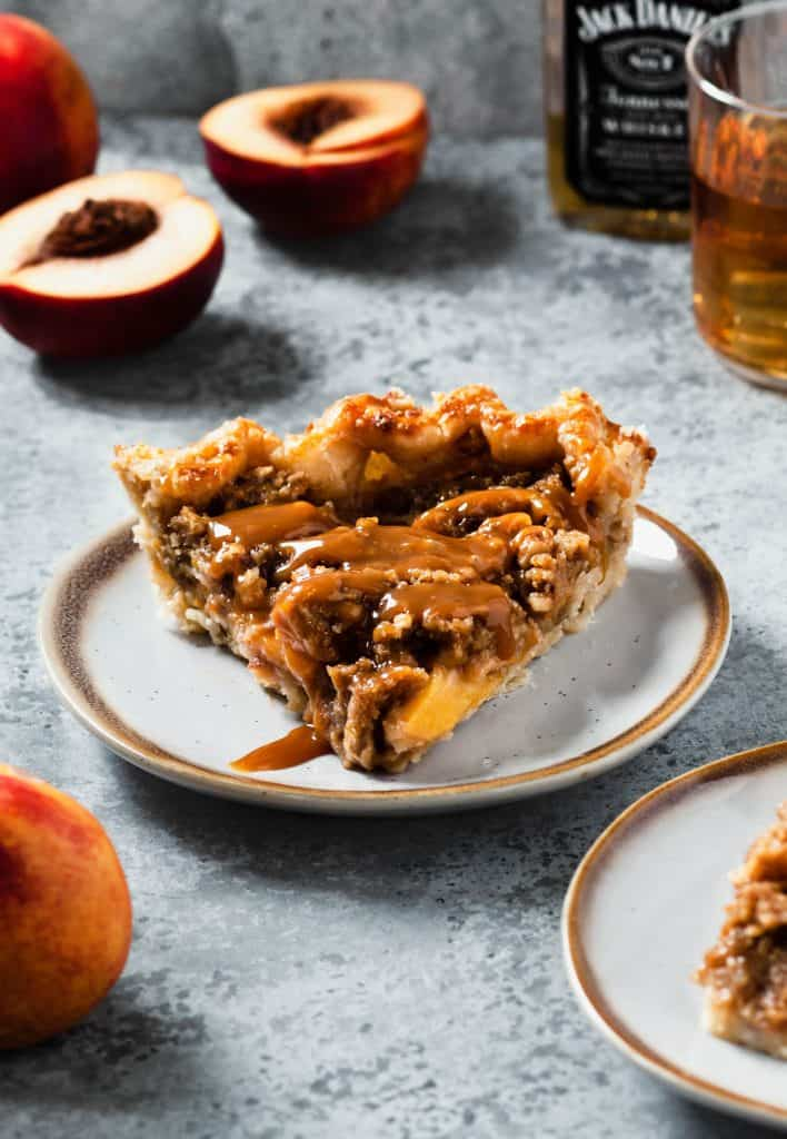 slice of peach crumble pie on white plate with metal background
