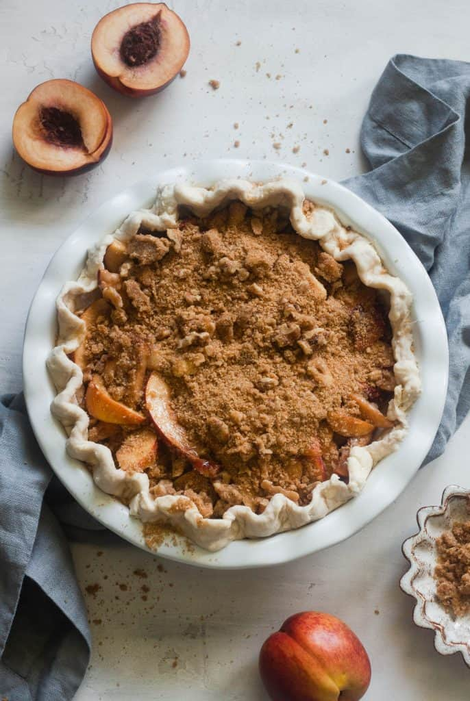 overhead shot of unbaked peach pie with crumble topping