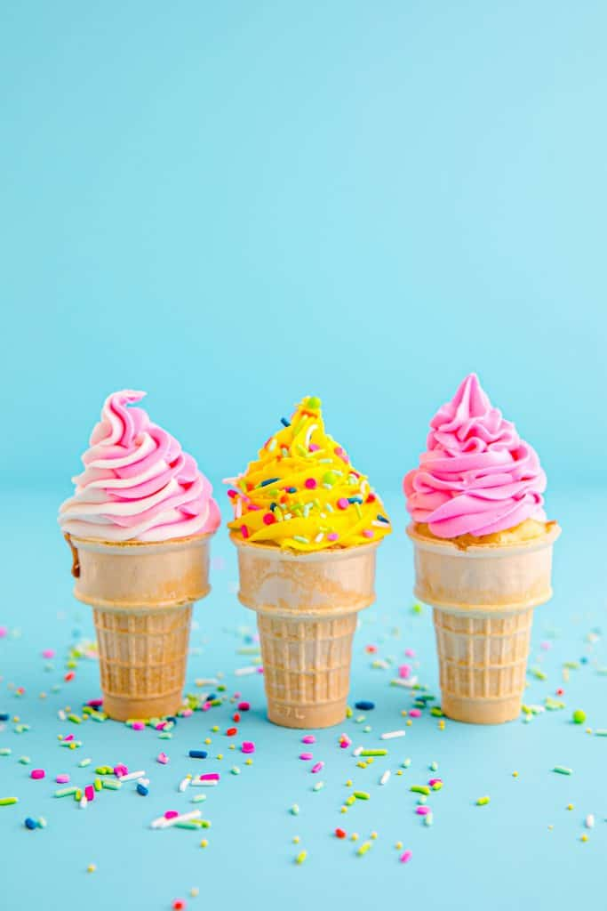 3 ice cream cone cupcakes with pink and yellow frosting