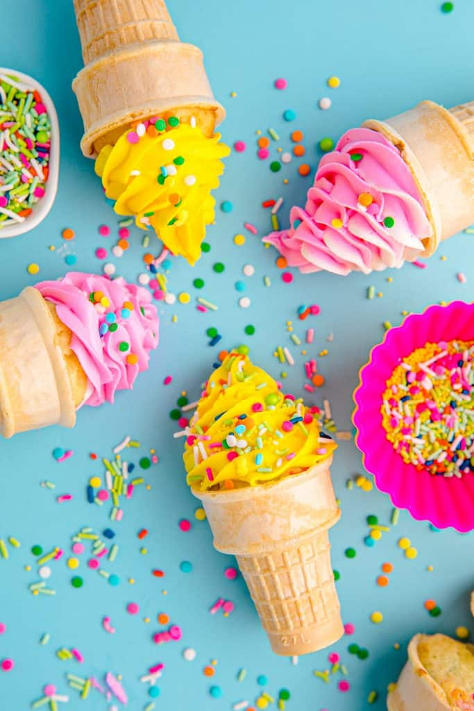 four ice cream cone cupcakes on their sides on blue background