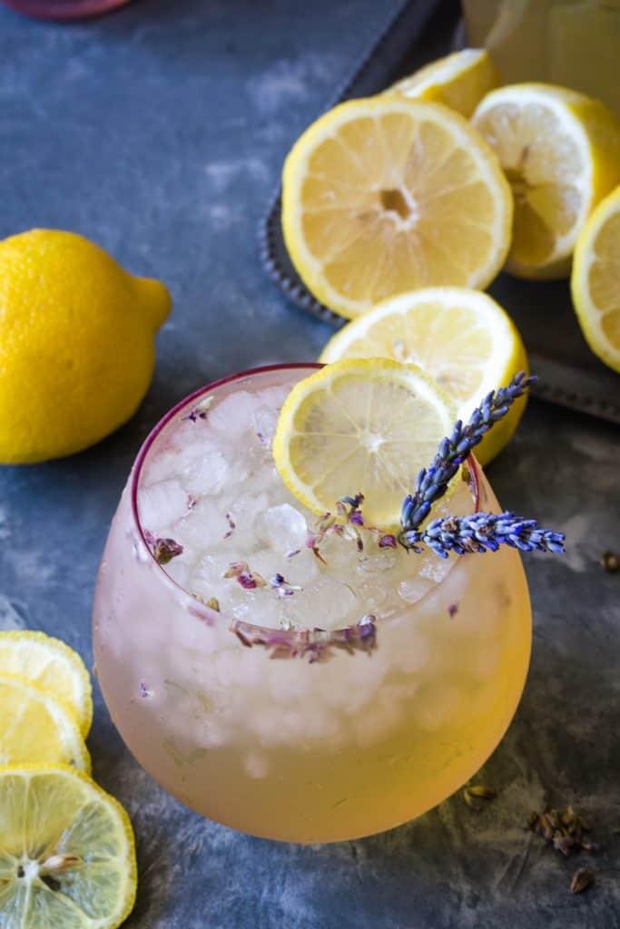 pink glass of lavender lemonade with lemon slices and fresh lavender