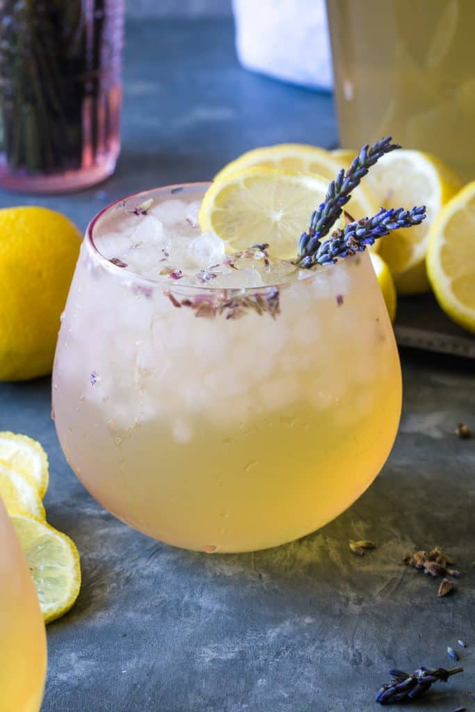 glass filled with ice and lavender lemonade on a metal background