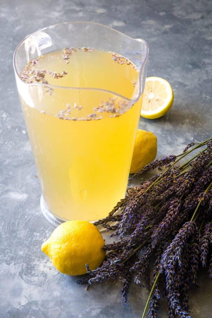 a large pitcher of lavender lemonade on a metal background