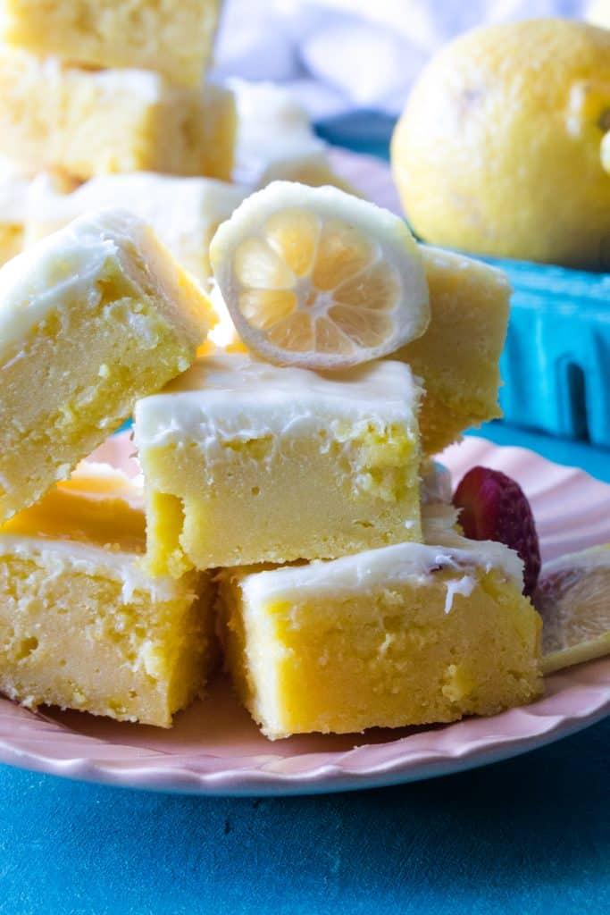 close up of lemon bars on pink plate