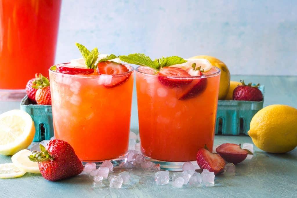 two glasses of strawberry lemonade on blue background