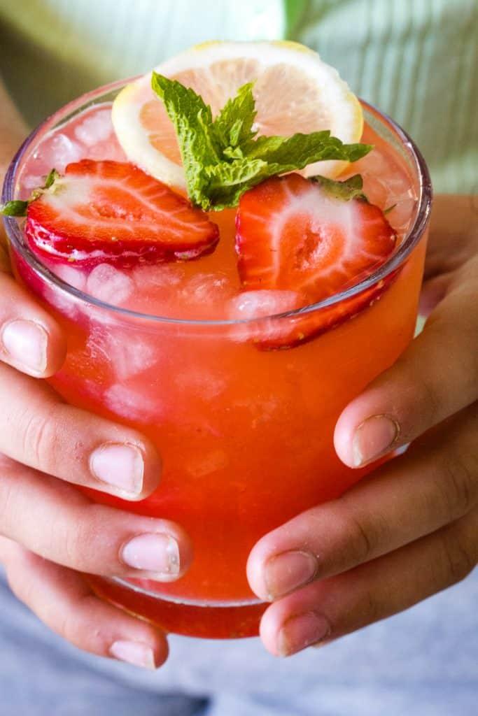 hands holding a glass of strawberry lemonade