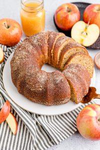 apple bundt cake on white cake plate sliced