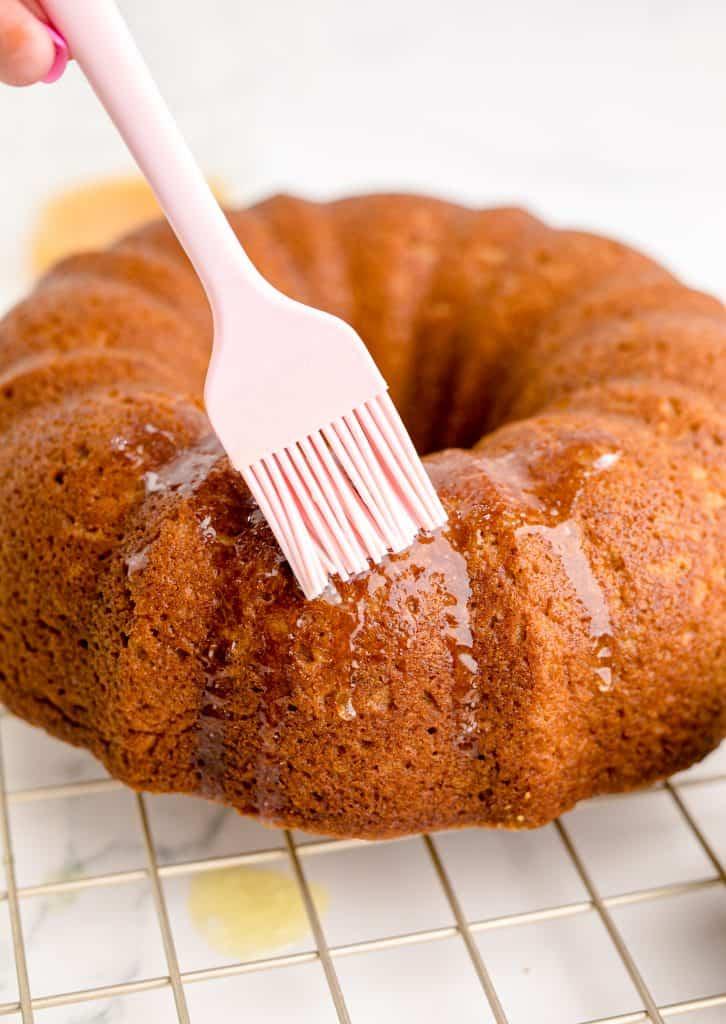 putting glaze onto the apple cider donut cake