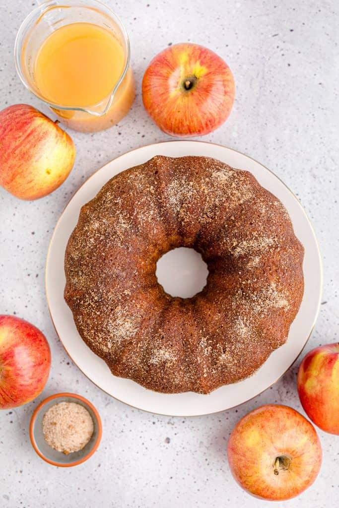overhead shot of apple cider donut cake on white cake plate