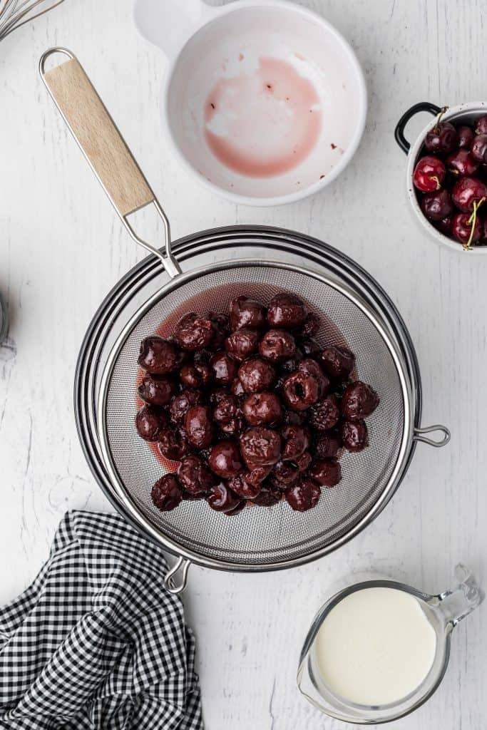 draining cherries in glass bowl