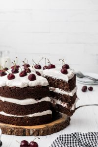 hand taking a slice of Black Forest cake on white background