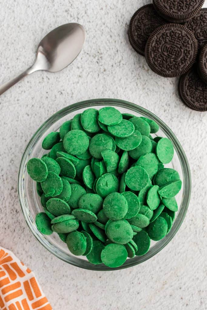 a glass bowl full of green melting chocolates