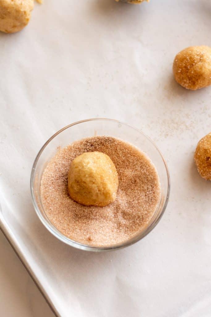 rolling dough ball into cinnamon and sugar
