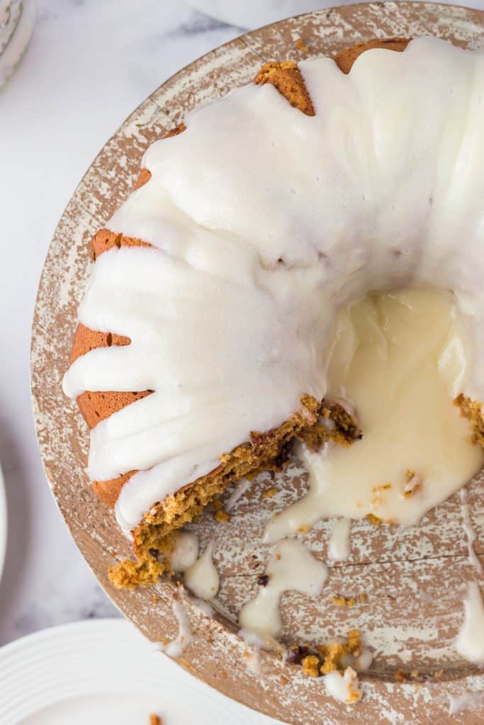 bundt cake with slice taken out on wooden cake plate